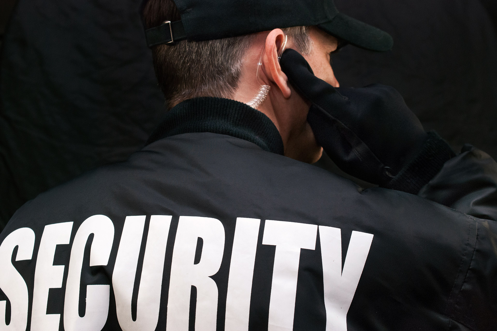 back of a security guard in uniform listening on an earpiece